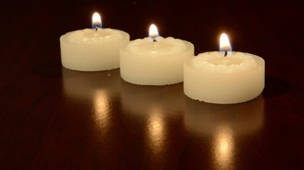 Three tea light candles burning on a table