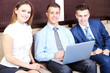 Young business people sitting on couch in office