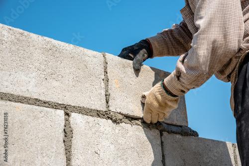 Leinwandbild Motiv worker build concrete wall by cement block and plaster