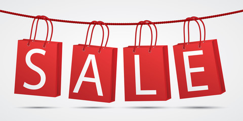 Realistic red shopping bags hanging on rope with text sale