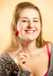 woman with toothy smile posing with decorative red heart