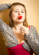 cute stylish woman holding red heart on stick at lips
