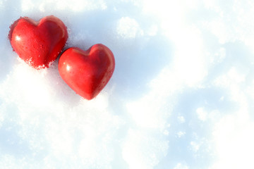 Two red frozen heart on snow background