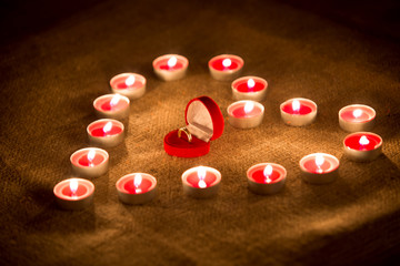 box with golden ring lying in heart made of candles