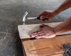 Carpenter nailing teak wood board by hammer