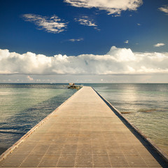 Path on the pier by the ocean with blue sky and clouds