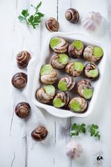 Escargots de Bourgogne, white wooden surface, close-up