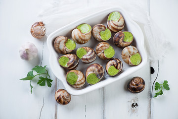 Bourgogne snails with garlic butter over white wooden background