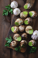 Snails with garlic butter on a rustic chopping board, above view