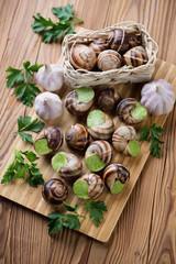Escargots de Bourgogne on a wooden cutting board