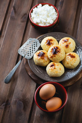 Curd pancakes with ingredients over rustic wooden background