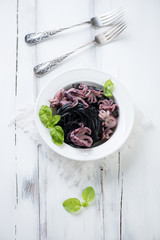Squid ink colored tagliatelle and octopuses, high angle view