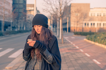 Beautiful young woman texting in the city streets