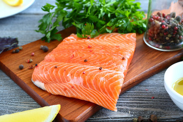 Raw fillet Salmon with greens and lemon on a board
