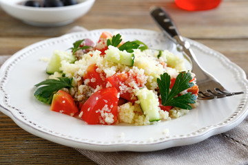 Salad with arabic couscous and vegetables on a white plate