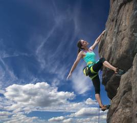 Elegant female alpine climber ascents natural rock