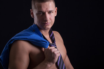 muscular sexy man posing in a tie on black background
