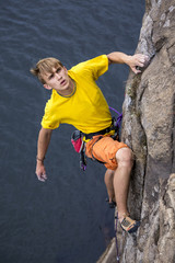 Young male rock climber hanging over the water and looking up