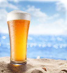 Ice beer glass in the sand.