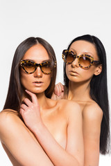 Two beautiful girl in sunglasses posing in the studio. Using adv