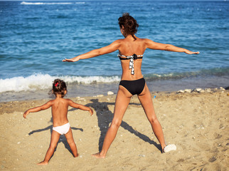 Mother and daughter doing exercise at the seaside.