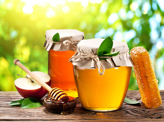 Glass cans full of honey, apples and combs.