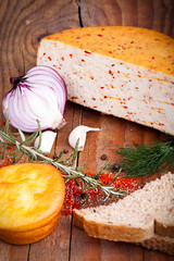 cheese, garlic herbs on the old wooden background