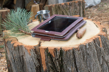 Tablet computer on wooden logs table with pine and mug
