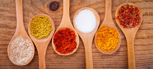 Assortment of powder spices on spoons on wooden background