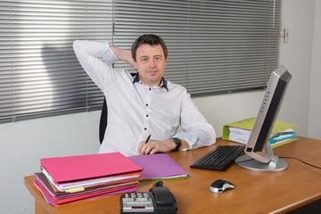 Homme à son bureau détendu, une main derrière la tête
