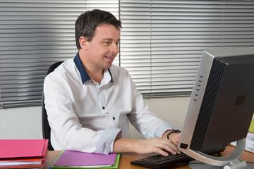 Homme à son bureau très content devant son écran