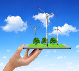 Hand holding digital tablet with a wind turbines and trees