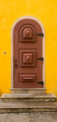 Old wooden door with metal hinges and lock on the yellow wall