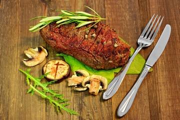 Beefsteak and Tableware on wood Board