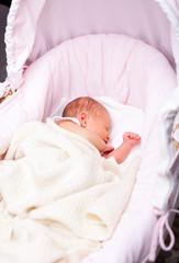 Newborn baby in a bassinet
