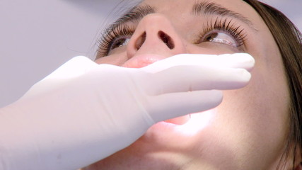 Closeup of woman being operated by dentist