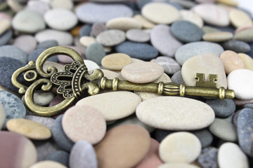 Old Brass key on a pebble beach