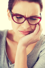 Young woman in eyeglasses with toothache.