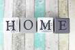 Home sign on a distressed wooden background with turquoise tones - 76245268