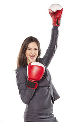 Happy business woman with boxing gloves in winning position