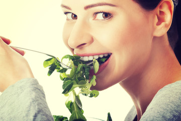Beautiful woman eating lettuce.
