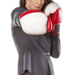 serious business woman with boxing gloves on a white background