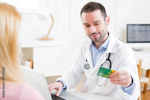 Young attractive doctor taking health insurance card - 76245629