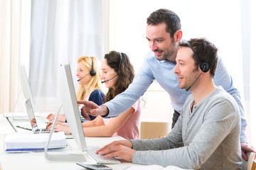 Manager training a young attractive people on computer