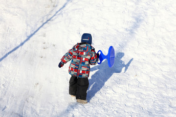 Kid climbing on a snowy hill