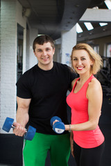 Cheerful couple with fitness dumbbells