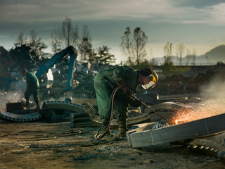welders cutting metal for recycling
