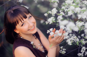 smiling woman in a spring garden holding flower