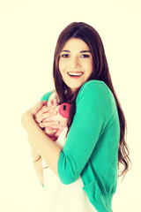 Young woman holding piggy-bank.