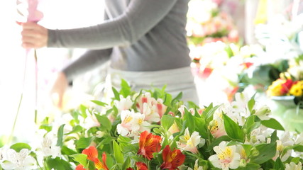 Woman making a bouquet of fresh flowers in a flower shop